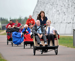Pictured: Public health and sport minister Aileen Campbell pedals Norman Ridley (81) and Amelia Franchi (14) followed by other Cycling Without Age users.<br /> <br /> Public health and sport minister Aileen Campbell took to the saddle to launch the Scotland-wide rollout of the Cycling without Age service, designed to get older people out and about.<br /> <br /> &copy; Dave Johnston / EEm