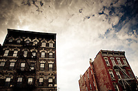 Colourful, old buildings loom in front of a partly cloudy blue sky in neighbourhood of Williamsburg, Brooklyn, NY, USA.