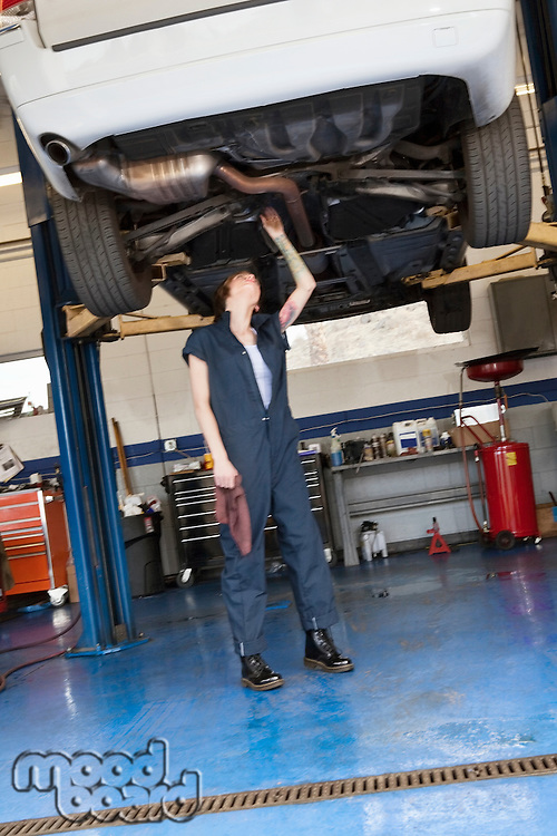 Young female mechanic working while standing under lifted car in workshop