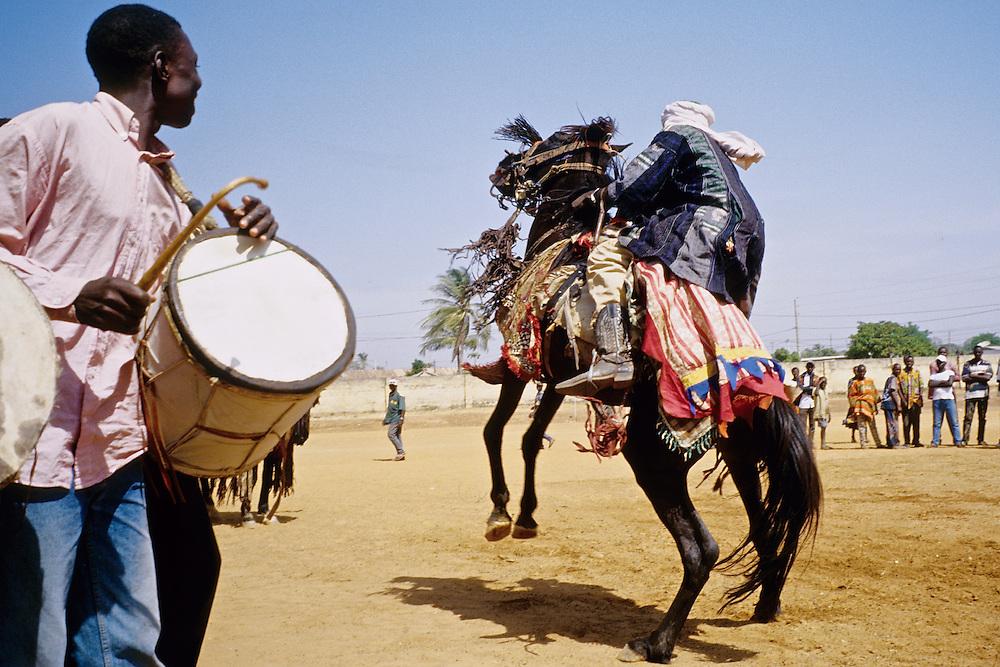 Enthronement of the king of Bariba. The traditional Gaani festival. The rider makes his horse dance to the rythm of the drums. The horse is finishing a courbette.<br />  <br /> Intronisation du roi des Bariba. La f&ecirc;te traditionnelle de la Gaani. Les cavaliers font danser leurs chevaux aux rythme des tambours. Le cheval descend d'une courbette.