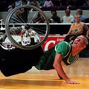 Australian wheelchair basketballer Troy Sachs watches his shot as he falls with his wheelchair attached to himself. Sydney Entertainment Centre, Sydney, Australian.