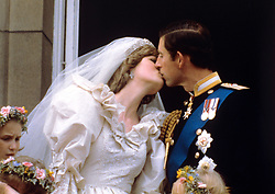 The newly married Prince and Princess of Wales (formerly Lady Diana Spencer) kiss on the balcony of Buckingham Palace after their wedding ceremony at St. Paul's cathedral.