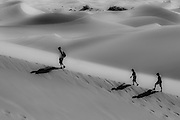 Hikers on sand dunes in Death Valley National Park, California