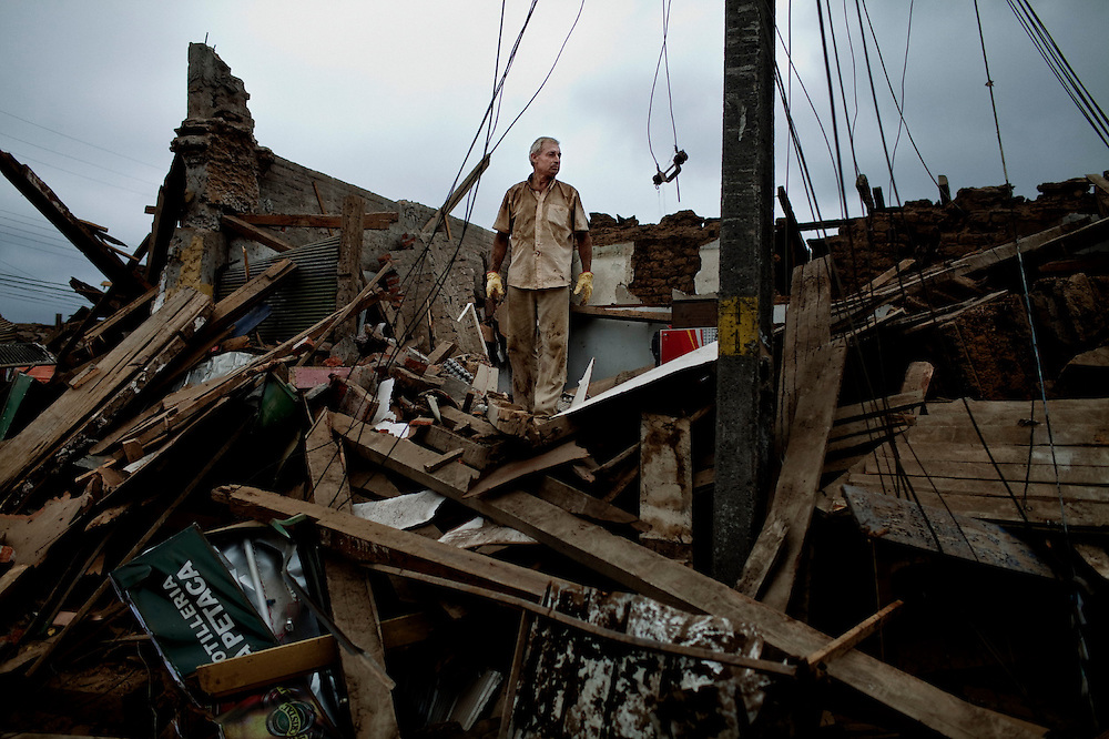 An earthquake survivor inspects the remains of his house that resulted completely destroyed after the earthquake in Constitucion, Chile. Feb 28, 2010.