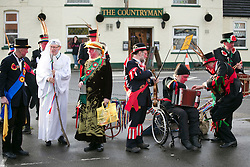 "© Licensed to London News Pictures.10/1/2015.Sharnford, Leicestershire, UK. The annual plough tour by the Hinckley Bullockers took place today. Pictured, dancing outside the Countrymam Public House in Sharnford. Visiting seven venues around Leicestershire the Bullockers, some with with red painted faces, are seen pulling their decorated plough along the street before stopping to perform traditional dances.<br /> <br /> HISTORY -  On the first Monday after Twelfth Night - Plough Monday - the plough was prepared for the new season, dressed in gaudy ribbons and taken in procession around the villages. In South West Leicestershire the men pulling the plough, who ""raddled"" their faces, were known as Plough Bullocks and were aided and abetted by dancers who danced dances peculiar to the Eastern Counties. The Plough Bullocks and the Molly Dancers were last seen in this area at the turn of the century in Sapcote.<br />  Traditionally, the Plough Bullockers would stop at public houses, farms and large houses, dance and/or sing and demand recognition in the form of cash donations or drink. If neither was forthcoming the offending landlord's drive was ploughed up. Photo credit : Dave Warren/LNP"