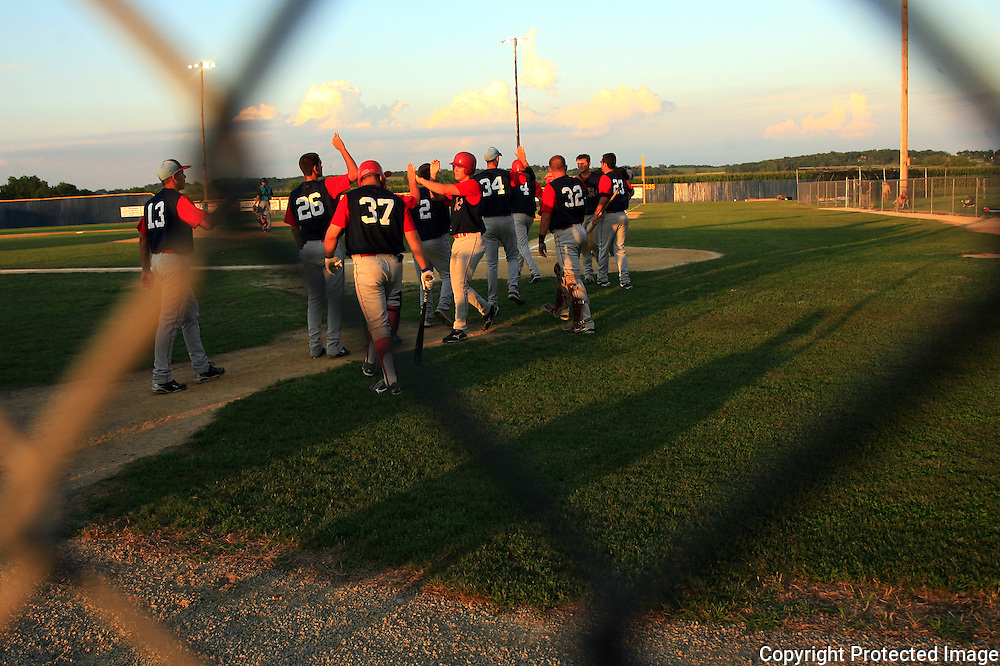 The Clarinda A's celebrate one of their 9 runs against the Omaha Diamond Spirit during a June tournament game.  photo by David Peterson