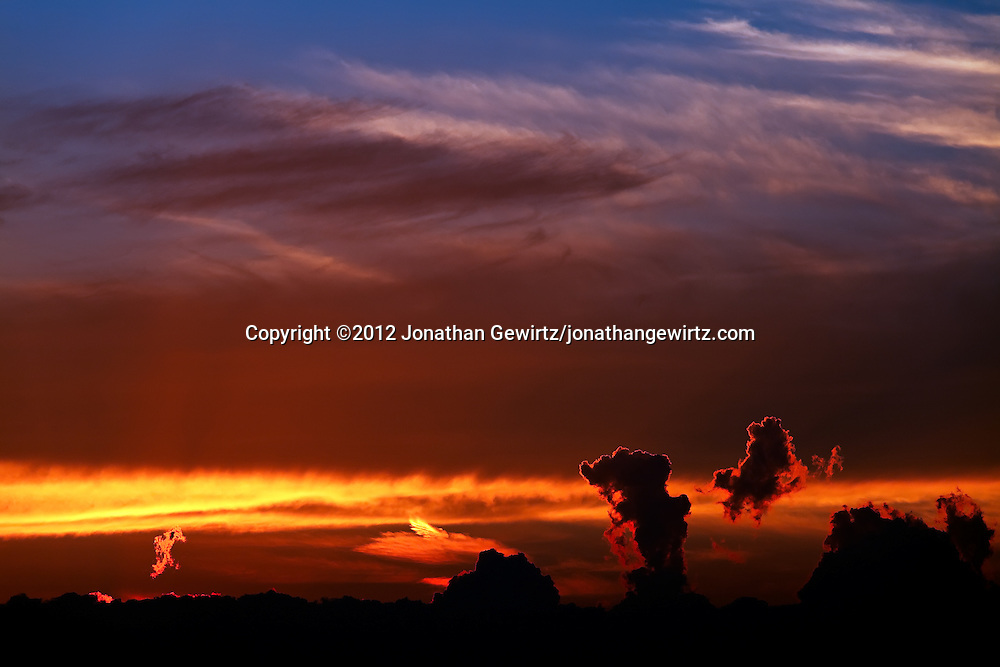 Billowing layers of distant clouds are dramatically backlit by warm orange light from the setting sun. WATERMARKS WILL NOT APPEAR ON PRINTS OR LICENSED IMAGES.