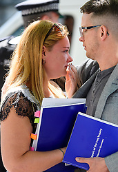 © Licensed to London News Pictures. 06/07/2016. London, UK. VICTORIA JONES, sister of Leading aircraftman Martin Beard who was killed in the Iraq war, holds a copy of the Chilcot Report as she is comforted by a friend outside the QE2 conference centre in London where the long-awaited Chilcot inquiry into the war in Iraq has been released. Photo credit: Ben Cawthra/LNP