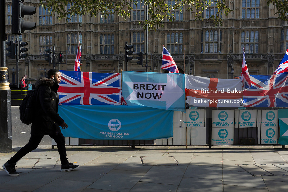On the day that the EU in Brussels agreed in principle to extend Brexit until 31st January 2020 (aka 'Flextension') and not 31st October 2019, a pedestrian walks past Brexit Party flags and banners during a Brexit protest outside parliament, on 28th October 2019, in Westminster, London, England.