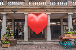 "© Licensed to London News Pictures. 14/02/2018. LONDON, UK. A giant chubby heart balloon is seen at Covent Garden as part of ""Chubby Hearts Over London"",  a design project conceived by Anya Hindmarch.  Supported by the Mayor of London, the British Fashion Council and the City of Westminster giant chubby heart balloons will be suspended over (and sometimes squashed within) London landmarks as a declaration of love to the city starting on Valentine's Day and continuing throughout London Fashion Week.   Photo credit: Stephen Chung/LNP"