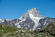 Near Lötschen Pass, see the Bietschhorn (3934 m/12,907 ft) in canton Valais/Wallis, Switzerland, the Alps, Europe. The northeast and southern slopes of the Bietschhorn are in Jungfrau-Aletsch Protected Area, a UNESCO World Heritage Site. Kandersteg is a great base for hiking; an epic hike from Selden in Bern canton traverses Lötsch glacier and Lötschenpass (Lötschepass) to neighboring Lötschental in Valais canton; hiking poles recommended for snow and rocks. The walk starts with a reserved Postbus ride from Kandersteg to Selden (in Gasterntal / Gasteretal / Gasterental), climbs 1350 meters, descends 925 m, and ends 13 km later at Lauchernalp lift station, which descends to Wiler in Lötschental, to reach Goppenstein via Postbus, back to Kandersteg via train. You can also reverse the route or stay overnight in dorms at Lötschepass hut.