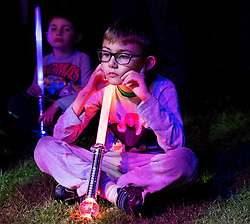 © Licensed to London News Pictures.22/08/15<br /> Castle Howard, North Yorkshire, UK. <br /> <br /> A young boy with a glowing toy sword covers his ears as he sits on the grass in front of the main stage during the 25th anniversary of the Castle Howard Proms event near York. The theme of the event this year is a commemoration of the 75th anniversary of the Battle of Britain and the 70th anniversary of VE day and brings an evening of classic musical favourites celebrating Britishness to the lawns of Castle Howard.<br /> <br /> Photo credit : Ian Forsyth/LNP
