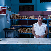 René Alcair, of  Habana Vieja, Cuba, pauses for a rare break while working on a sweltering summer day at the desk of a government-run bread dispensary in his neighborhood, where he has both baked and distributed bread for 11 years.  A remaining outpost of the post-revolution rationing system, the dispensary distributes the allotted weekly amounts of bread rationed to registered residents of the neighborhood. Alcair marks down the amounts received in each person's paper government rations booklet, or libreta, as they come through each day.  Extra bread can also be purchased for a few cents in the Cuban peso currency.  Photo by Jen Klewitz