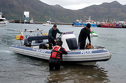 Cape Town - 180813 - The Hout Bay fishing community are distraught and tensions are running high after an alleged poacher was shot at see while being apprehended by the authorities In pic the Police Diving unit along with a dog set off in search of the missing person  Photographer - Tracey Adams - ANA African News Agency