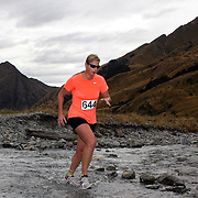 Runner Julia Blanchard crosses Moke Creek on the Ben Lomond High Country Station during the Pure South Shotover Moonlight Mountain Marathon and trail runs. Moke Lake, Queenstown, New Zealand. 4th February 2012. Photo Tim Clayton