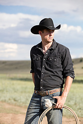 hot cowboy with a lasso on a ranch