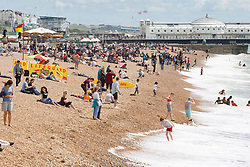 © Licensed to London News Pictures. 23/07/2017. Brighton, UK. Members of the public take advantage of the moments of sunshine to spend time on the beach in Brighton and Hove. Photo credit: Hugo Michiels/LNP