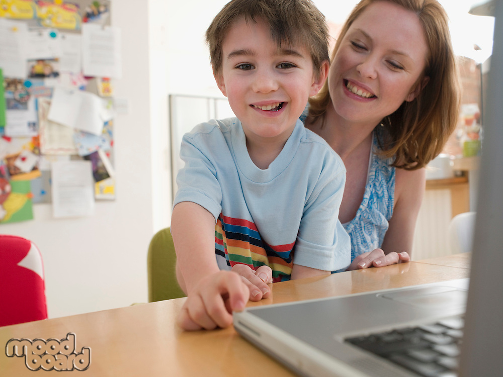 Mother and Son at Table With Laptop