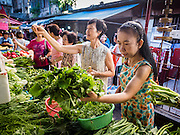 29 JUNE 2015 - BANGKOK, THAILAND:  People shop for fresh vegetables in the Bang Chak Market in Bangkok. The Bang Chak Market serves the community around Sois 91-97 on Sukhumvit Road in the Bangkok suburbs. About half of the market has been torn down, vendors in the remaining part of the market said they expect to be evicted by the end of the year. The old market, and many of the small working class shophouses and apartments near the market are being being torn down. People who live in the area said condominiums are being built on the land.    PHOTO BY JACK KURTZ