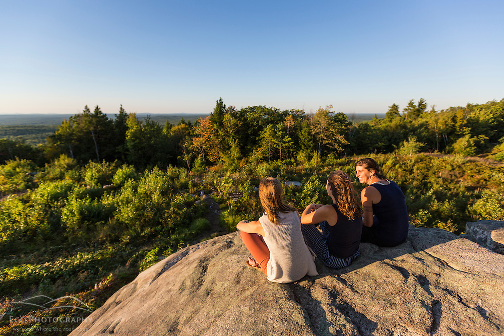 Three women enjoying the view from the summit of Mount Agamenticus in York, Maine.