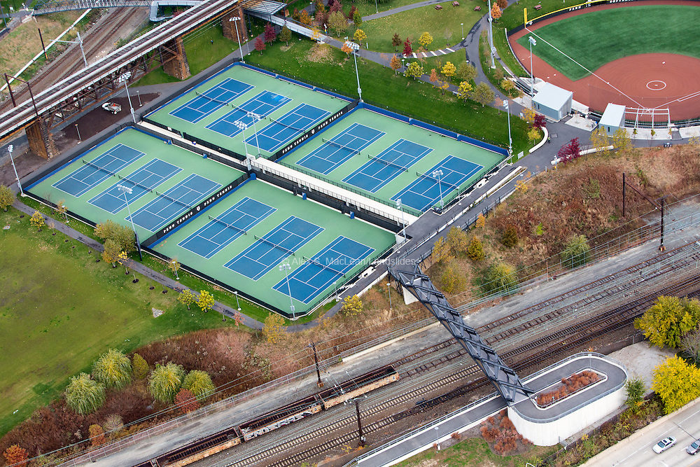 A pedestrian path crosses over rail lines to tennis courts at Penn Park. Park designed by landscape architecture firm Michael Van Valkenburgh Associates