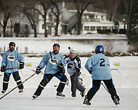 The Bumbles and Munny Shot teams battle on the ice for a spot in the semi final game during Sunday's New England Pond Hockey Classic.  (Karen Bobotas/for the Laconia Daily Sun)