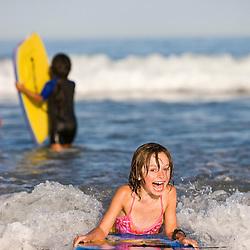 A young girl boogie boarding at Hampton Beach in Hampton Beach, New Hampshire.