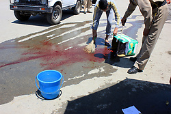 July 2, 2017 - Anantnag, Jammu & Kashmir, India - A policeman washing blood stains from roadside in General Bus Stand, after Suspected militants have shot police constable of the Jammu and Kashmir Police in a broad daylight at General bus Stand  in Anantnag. (Credit Image: © Muneeb Ul Islam/Pacific Press via ZUMA Wire)