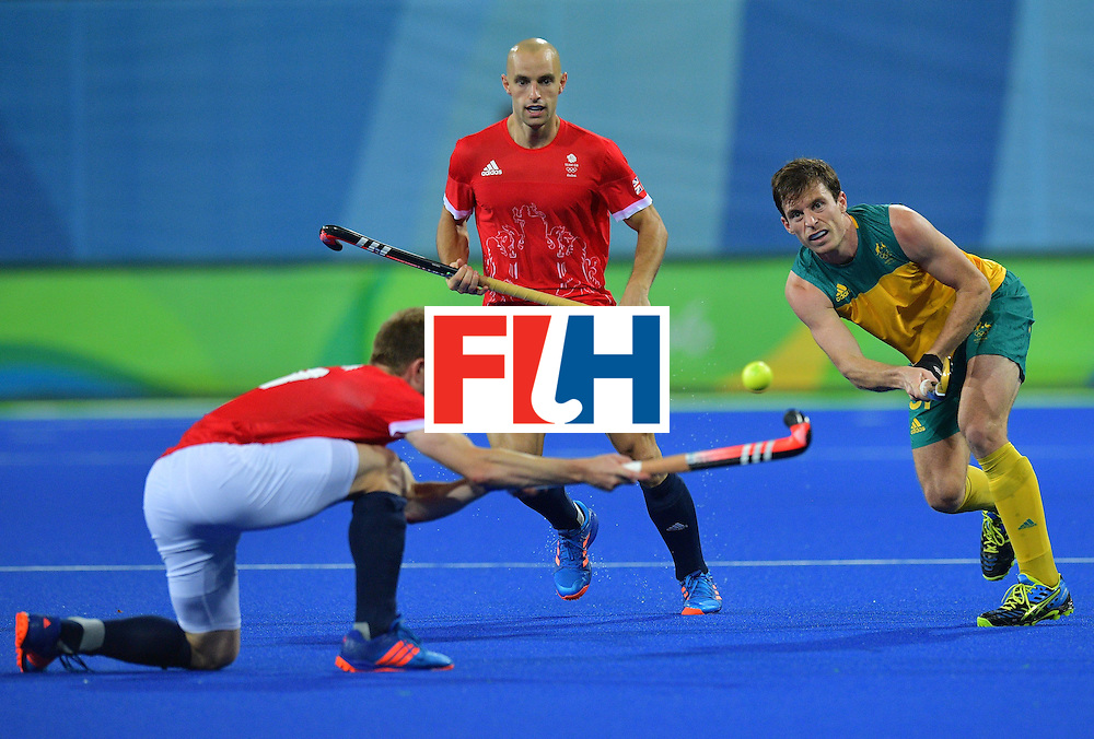 Australia's Fergus Kavanagh (R) hits the ball past Britain's Barry Middleton (L) as Britain's Nick Catlin looks on during the men's field hockey Britain vs Australia match of the Rio 2016 Olympics Games at the Olympic Hockey Centre in Rio de Janeiro on August, 10 2016. / AFP / Carl DE SOUZA        (Photo credit should read CARL DE SOUZA/AFP/Getty Images)