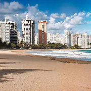 Clouds drift past the high rises comprising the trendy Condado district of scenic San Juan, Puerto Rico, giving way to an expanse of tropical ocean and Caribbean sand.<br /> <br /> This is a panoramic composite.
