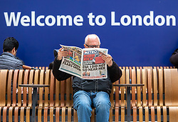 © Licensed to London News Pictures. 12/03/2020. London, UK. A train travellers reads the news at Victoria Station as the World Health Organization declares Covid19 the Coronavirus disease a Pandemic and US President Donald Trump bans all travel from Europe except the UK as fears over the Coronavirus continues. Photo credit: Alex Lentati/LNP