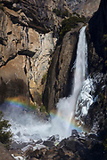 A rainbow forms in Lower Yosemite Falls in Yosemite National Park, California, on a cold winter morning. This 320-foot (98 meter) waterfall is one of three sections that together make up Yosemite Falls, the tallest measured waterfall in North America with a total height of 2,425 feet (739 meters).
