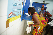 A woman picks up medicine to treat her daughter's diarrhea from the pharmacy of the Koumassi Grand Campement health center in Abidjan, Cote d'Ivoire on Thursday July 18, 2013.
