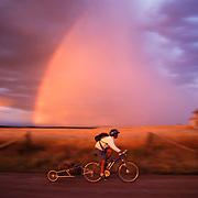 A photo of a man mountain biking past a rainbow and an old barn near Driggs Idaho at sunset