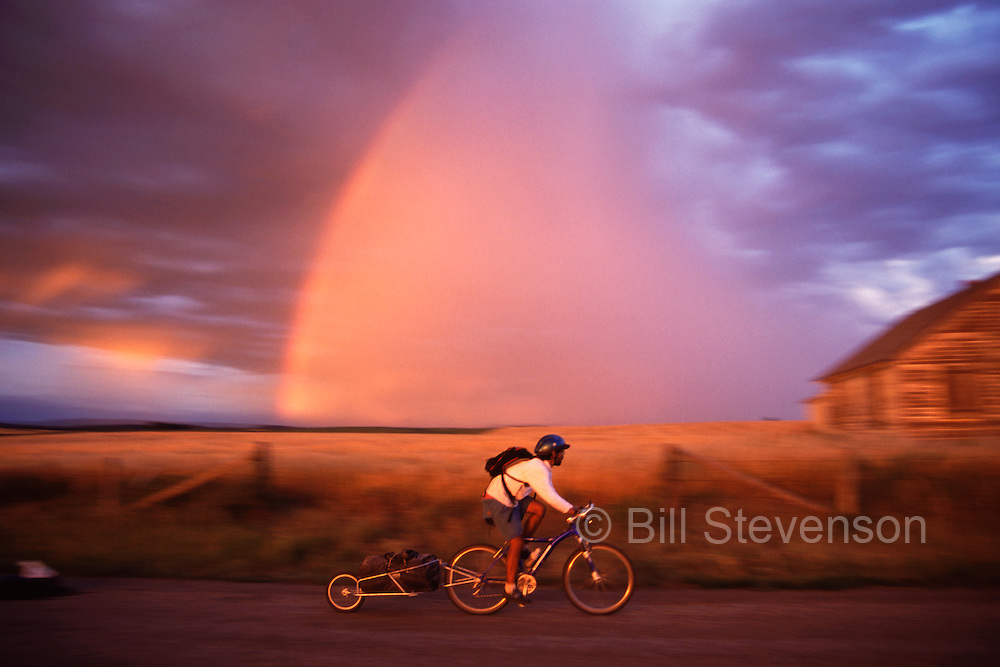 A photo of a man mountain biking past a rainbow and an old barn near Driggs Idaho at sunset