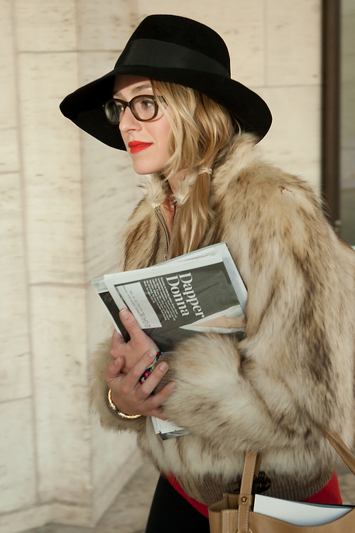 An attendee leaving the Mercedes-Benz New York Fall Fashion Week show wearing a black fedora and a fur jacket.