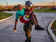 A member of the U.S. Coast Guard carries a man out of Marsh Harbour Medical Care Center on Friday, September 6, 2019. The U.S. and others are evacuating people from Great Abaco Island after Hurricane Dorian tore through the Bahamas.