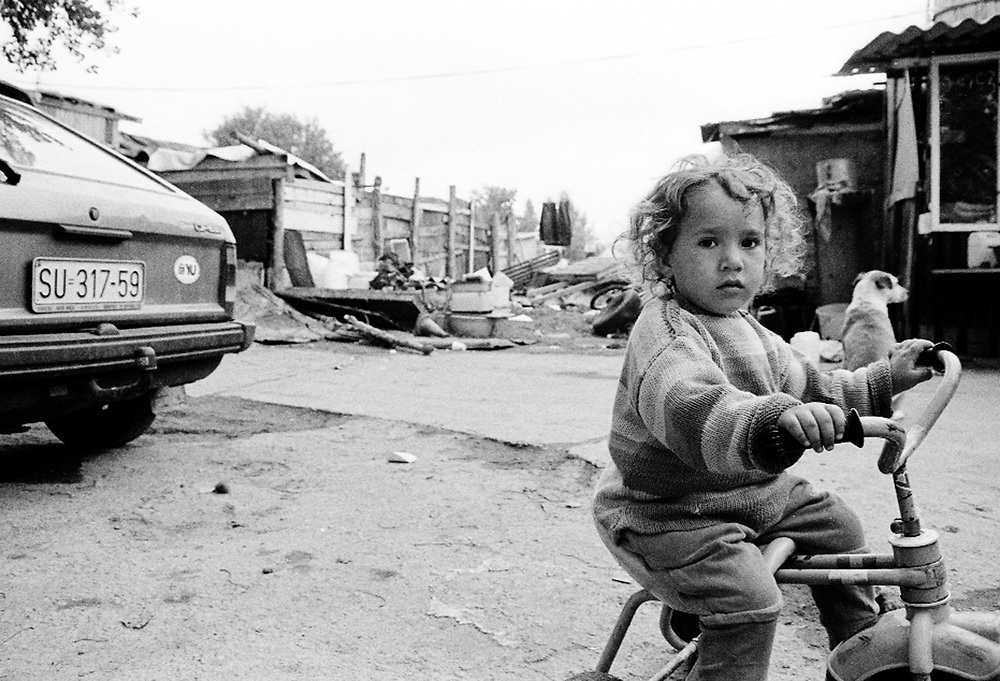Roma children in a makeshift camp in Kraljevo. ..Romas children do not receive the same attention as the other IDPs children: they do not go to school and they do not receive any assistance as far as health is concerned. Because the families did not have documents, they could not be registered officially as IDPs...During the summer1999, over 245,000 Serbs and Roms fled to Serbia and Montenegro from or within Kosovo in fear of reprisals from the majority Albanian population, after NATO air strikes had forced the withdrawal of Yugoslav. In 2003, less than 2% of them had returned and a large number of these internally displaced persons (IDPs) were still living in camps in very difficult conditions..In addition, around 5,000 IDPs, mainly of Roma ethnicity, are living in unrecognized collective centres, makeshift huts, corrugated metal containers and other substandard shelters. .This work  was meant to look at how the life of children and young adults is affected by the fact that they are IDPs. I asked myself more specifically what would be different for these children/young adults from the 'normal' people of their age as far as education, health, social life, family, 'love' life and leisure are concerned. ..Enfants roms dans un camp improvisé de Kraljevo. ..Les enfants roms ne vont pas à l'école et ne reçoivent aucune assistance médicale. Faute de papiers d'identité, ils n'ont pu être officiellement enregistrés en tant qu'IDP...Pendant l'été 1999, plus de 245 000 serbes et roms ont fuit le Kosovo pour chercher refuge en Serbie ou au Montenegro, par peur de représailles de la part de la majorité de la population albanaise après que les forces de l'OTAN aient forcé l'armée yougoslave à se retirer. En 2003, moins de 2% d'entre eux étaient rentrés chez eux et le plus grand nombre de ces 'déplacés' (IDPs) vivaient encore dans des centres d'accueil dans des conditions très difficiles..Environ 5 000 IDPs, la plupart romas, vivent dans des centres non reconnus faits de containe