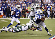 Indianapolis Colts wide receiver Donte Moncrief (10) tries to elude tackle attempts by New York Jets cornerback Darrelle Revis (24) and leaping New York Jets defensive back Buster Skrine (41) as he catches a third quarter pass for a gain of 15 yards during the 2015 NFL week 2 regular season football game against the New York Jets on Monday, Sept. 21, 2015 in Indianapolis. The Jets won the game 20-7. (©Paul Anthony Spinelli)