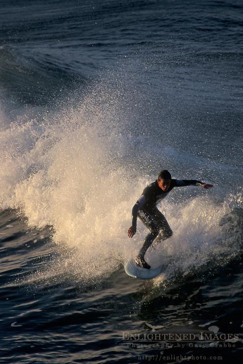 Surfers riding waves at sunrise+Oceanside Beach, Oceanside, San Diego County, CALIFORNIA