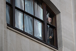 © Licensed to London News Pictures . 27/09/2018 . London , UK . TOMMY ROBINSON looks out of a second floor window of the Old Bailey at supporting crowds on the street outside , ahead of the start of his retrial . Supporters of and those against former EDL leader Tommy Robinson (real name Stephen Yaxley-Lennon ) outside the Old Bailey , as Robinson faces a retrial for Contempt of Court following his actions outside Leeds Crown Court in May 2018 . Robinson was already serving a suspended sentence for the same offence when convicted in May and served time in jail as a consequence , but the newer conviction was quashed by the Court of Appeal and a retrial ordered . Photo credit: Joel Goodman/LNP