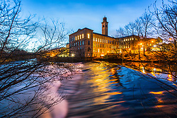 © Licensed to London News Pictures. 25/01/2018. Saltaire UK. The Salts Mill building reflects into the River Aire at dawn this morning in the World Heritage site of Saltaire village in Yorkshire. Photo credit: Andrew McCaren/LNP