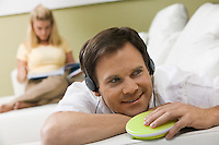 Man Listening to Music While Wife Reads