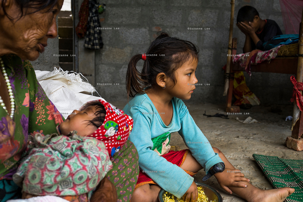 Aastha Baniya (6, in blue) has lunch while her grandmother Bhagawati Baniya (56) cradles her youngest sister Sapana Baniya (2 months) in their temporary home in Chautara, Sindhupalchowk, Nepal on 29 June 2015. The three girls lost their mother during the April 25th earthquake that completely levelled their house. Aastha was buried under the rubble together with her mother but Aastha survived. As their father Ratna Baniya (28) cannot care for the children on his own, SOS Childrens Villages has since been supporting the grandmother with financial and social support so that she can manage to raise the children comfortably and ensure that they will all be schooled. Photo by Suzanne Lee for SOS Children's Villages