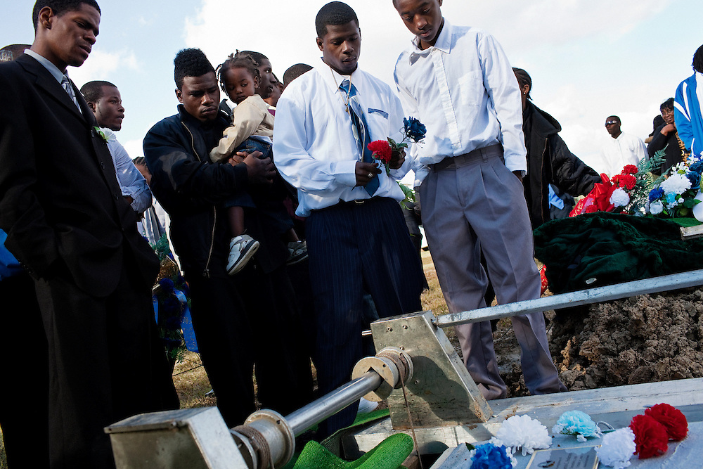 """Friends and family of Demetrius """"Butta"""" Anderson, 18, pay their last respects as his body is lowered into the ground at the cemetery on the outskirts of Greenwood, Mississippi on Friday, November 5, 2010. Butta was shot and killed on October 27, 2010."""