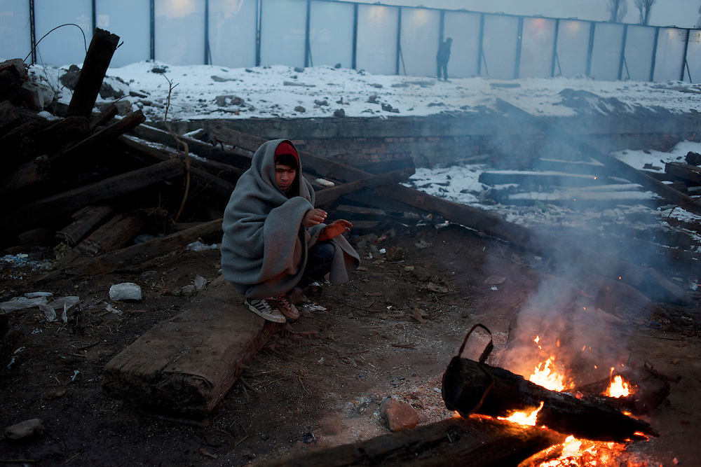 A migrant keeps warm near a open fire outside the abandoned warehouses in central Belgrade. The toxic old railway sleepers scattered around the area are been burned in bonfires used as main source of heat inside and outside the makeshift shelters.