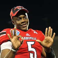 Louisville Cardinals quarterback Teddy Bridgewater (5)  celebrates on the podium after the NCAA Football Russell Athletic Bowl football game between the Louisville Cardinals and the Miami Hurricanes, at the Florida Citrus Bowl on Saturday, December 28, 2013 in Orlando, Florida. Louisville won the game by a score of 36-9. (AP Photo/Alex Menendez)