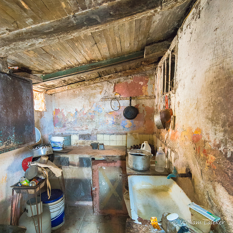 A kitchen in a Mantanza home with a wooden roof/ceiling that leaks when it rains. To cook, the residents use a hot plate and a popular method in Cuba: a crock pot cooker.