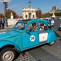 A sightseeing car passes through the Place du Carrousel by the Louvre Museum with the Arc de Triomphe du Carrousel in the background.