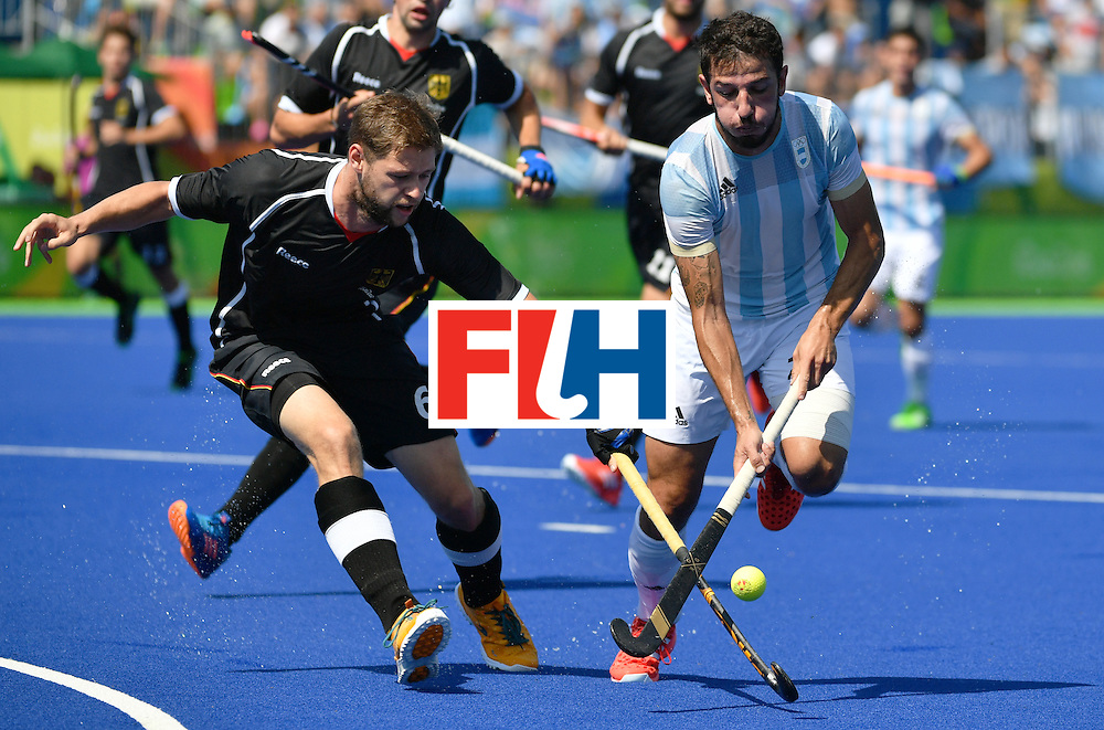 Germany's Martin Haner (L) vies with Argentina's Manuel Brunet during the men's semifinal field hockey Argentina vs Germany match of the Rio 2016 Olympics Games at the Olympic Hockey Centre in Rio de Janeiro on August 16, 2016. / AFP / Pascal GUYOT        (Photo credit should read PASCAL GUYOT/AFP/Getty Images)